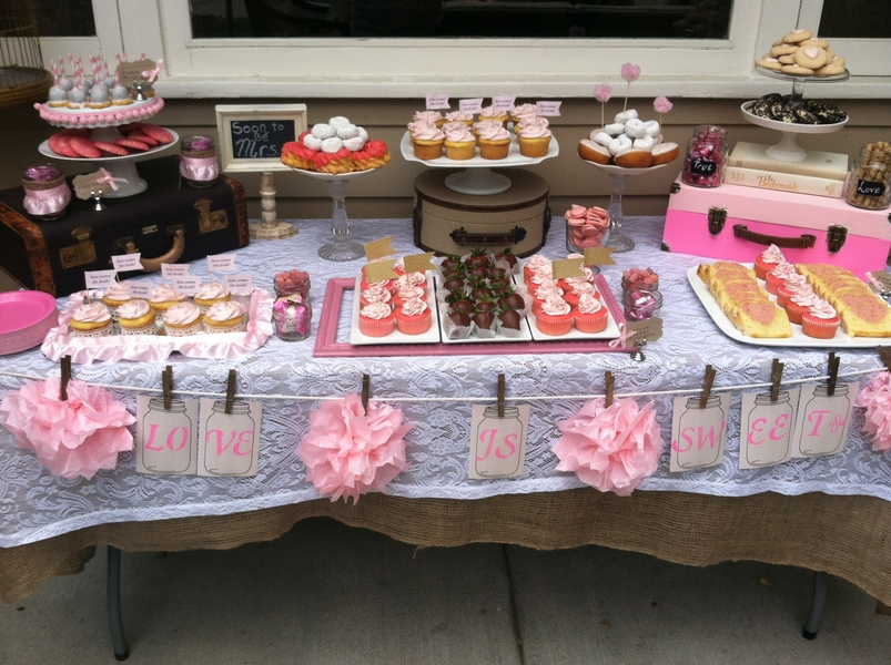 lots of pink and red sweets vintage suitcases and cute details like cupcake flags dessert tags and a table banner make this dessert table a sweet tooths
